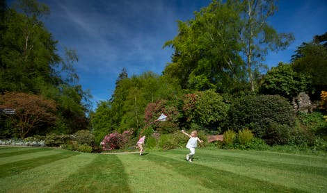 A woman and her two children enjoy playing on the South Lawn Hillsborough Castle and Gardens on a bright sunny day