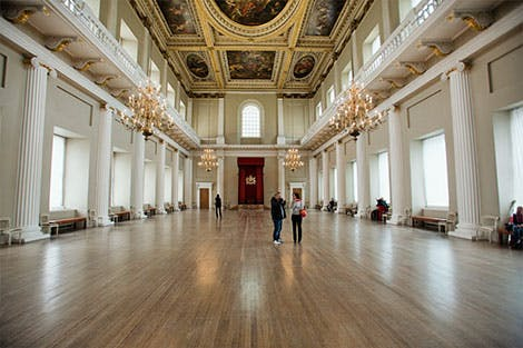 Photograph of visitors in the main hall of the Banqueting House
