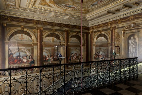 The staircase was painted by William Kent and completed in 1724. The walls depicts an elaborate arcaded gallery with figures behind a balustrade. Many are identifiable as members of King George I's court. The wrought iron balustrade is by Jean Tijou