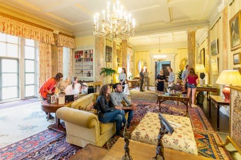 Visitors enjoying the State Drawing Room in Hillsborough Castle. A young couple are in the foreground sat on a 2-seater sofa, seemingly enjoying the views around them. The rest of the group are spread around the room; a HRP Explainer stands in the background. The room is a soft yellow, with marble-like columns, floral fabrics and wooden floor. Various rugs of different colours and patterns cover the floor. A chandelier hangs above.