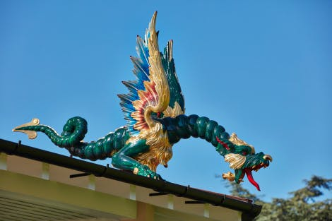 The Great Pagoda, showing a close up view of a dragon carving roof decoration. The dragon has a curled tail and its wings are spread. Colours are primarily green and gold with touches of blue and red, including a red tongue. The Pagoda reopened to the public on 13 July 2018 following a five-year restoration project.