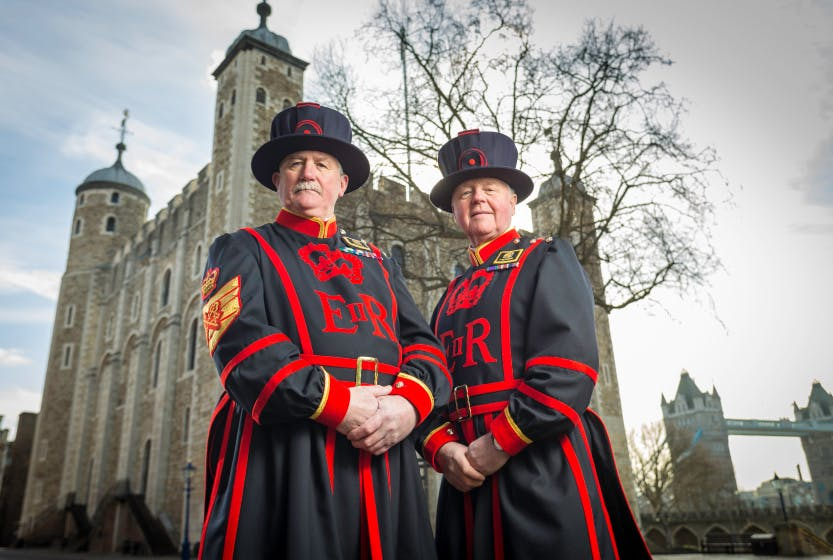 Two Yeoman Warders, also known as Beefeaters, stand in front of the White Tower of the Tower of London on a cloudy day
