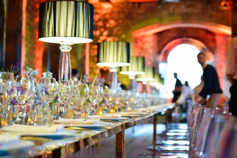 A long table decorated with dinner plates, glasses and lamps in a domed room