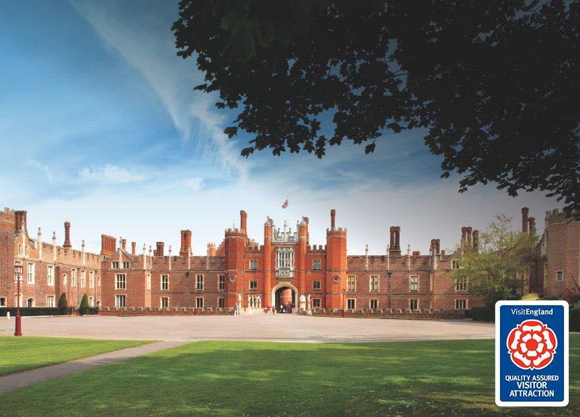 The Tudor buildings of Hampton Court Palace west front, under a blue partially cloudy sky. A lawn stretches out in front of the palace. The Visit England quality marquee logo is placed in the bottom-right hand corner of the image.