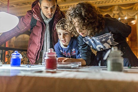 A family looking at pigments at an object handling table