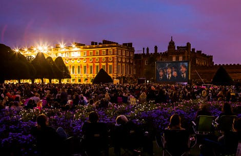 View of Hampton Court Palace with crowd in the foreground and Luna Cinema screen showing Harry Potter and the Philosopher's Stone in the background.