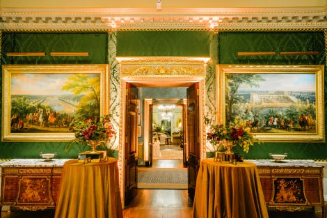 A view through the Throne Room through Stair Hall into the State Drawing Room. The walls are lined with rich green silk and two marble-topped tables stand either side of the open doors. Two poseur tables clothed in gold fabric frame the doorway. Each has a flower arrangement with greens, reds and yellow flowers within a gold vase, along with tealight candles. Two gold-framed landscape oil paintings also frame the doorway behind the flowers.