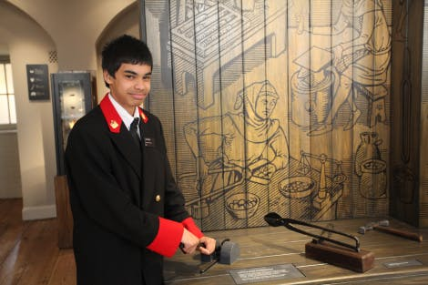 A warder holds one of the interactive display at the Coins and Kings exhibition.