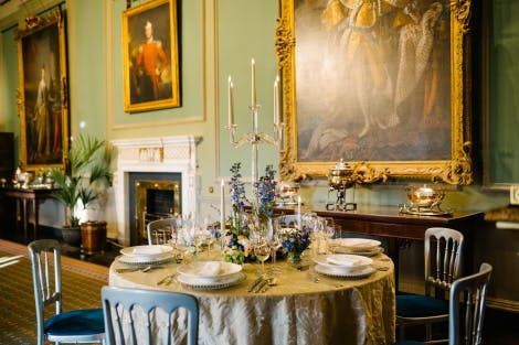 A 6ft round table situated in the State Dining Room and dressed for dinner. A silver damask cloth covers the table which is dressed with a glass candelabra, blue flowers and foliage. The corner of a large oil painting is visible in the background.