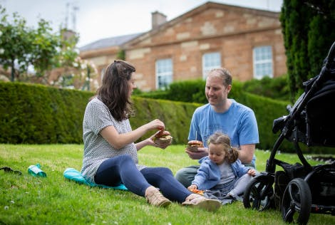 Family sitting on grass eating food