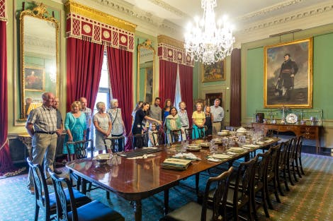 A group of visitors are being entertained by a HRP Explainer in the Red Room in Hillsborough Castle. In the centre of the room is a long Georgian dinning table that looks like it's currently being setup for a lavish dinner party, silver cutlery and crystal are visible on the table top. A Waterford Crystal chandelier hangs above the table and the walls are green. Red and gold curtains frame the tall windows and full-length gold-framed mirrors hang between them. A large rug with a flax flower design covers the wooden floor below.
