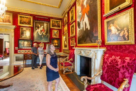 A lady stands in the foreground looking around her at the gold-framed paintings adorning the Red Room. The walls are covered in deep red silk damask and a marble fireplace is visible. An older couple can be seen in the background, also looking at the paintings.