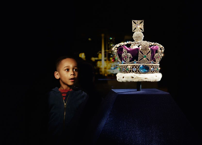 Young boy looking towards the Imperial State Crown in the Crown Jewels exhibition