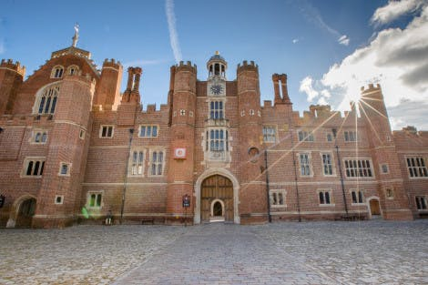 The Tudor buildings of Base Court at Hampton Court Palace, facing towards Clock Court, under a blue, partially cloudy sky with sunbeams stretched across the image. Anne Boleyn's Archway is also pictured.