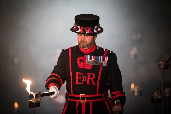 "The Tower Moat, showing Yeoman Warder Andy Shedden lighting an Armistice torch as part of his ceremonial duty at the ""Beyond the Deepening Shadow"" public event.   ""Beyond the Deepening Shadow: The Tower Remembers"" was a public act of remembrance to commemorate the centenary of the end of the First World War.  Each evening from 4 to 11 November 2018 the Tower moat was illuminated by 10,000 individual flames. The artistic installation included an exploration in sound of wartime alliances, friendship, love and loss. Beginning with a procession led by the Yeoman Warders, Armistice torches were lit to form a circle of light radiating from the Tower. A symbol of remembrance for the hundreds of thousands who died in the Great War."