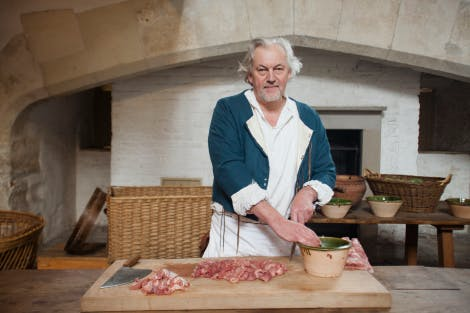 A food historian in period costume preparing traditional Tudor meat dish at a wooden table in the Tudor Kitchens at Hampton Court Palace.