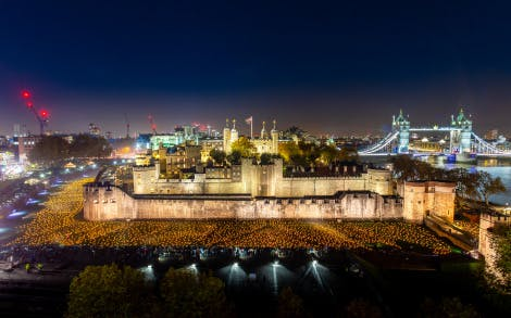 """The Tower Moat, showing an aerial view of the """"Beyond the Deepening Shadow"""" installation and surrounding lit-up city skyline.  """"Beyond the Deepening Shadow: The Tower Remembers"""" was a public act of remembrance to commemorate the centenary of the end of the First World War.  Each evening from 4 to 11 November 2018 the Tower moat was illuminated by 10,000 individual flames. The artistic installation included an exploration in sound of wartime alliances, friendship, love and loss. Beginning with a procession led by the Yeoman Warders, Armistice torches were lit to form a circle of light radiating from the Tower. A symbol of remembrance for the hundreds of thousands who died in the Great War."""