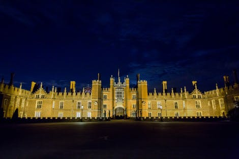 West front of Hampton Court Palace at night under a dark blue sky