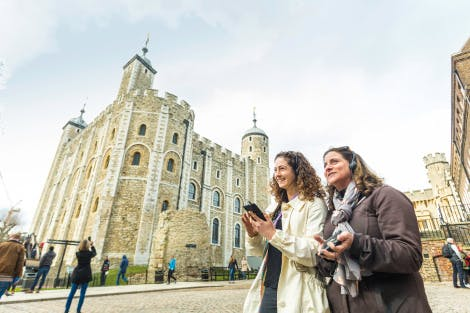 The White Tower, looking north-west towards the Wardrobe Tower. Showing two young women visitors in the foreground, happily using digital video guide tour devices.