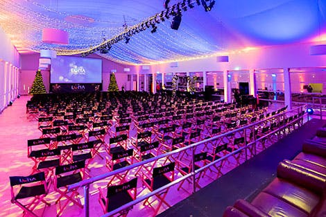 Luna Winter Cinema at Kensington Palace, showing a large event space lit in purple and pink. Chairs are arranged theatre-style and there is a large cinema screen at the far end, which is flanked by two Christmas trees.