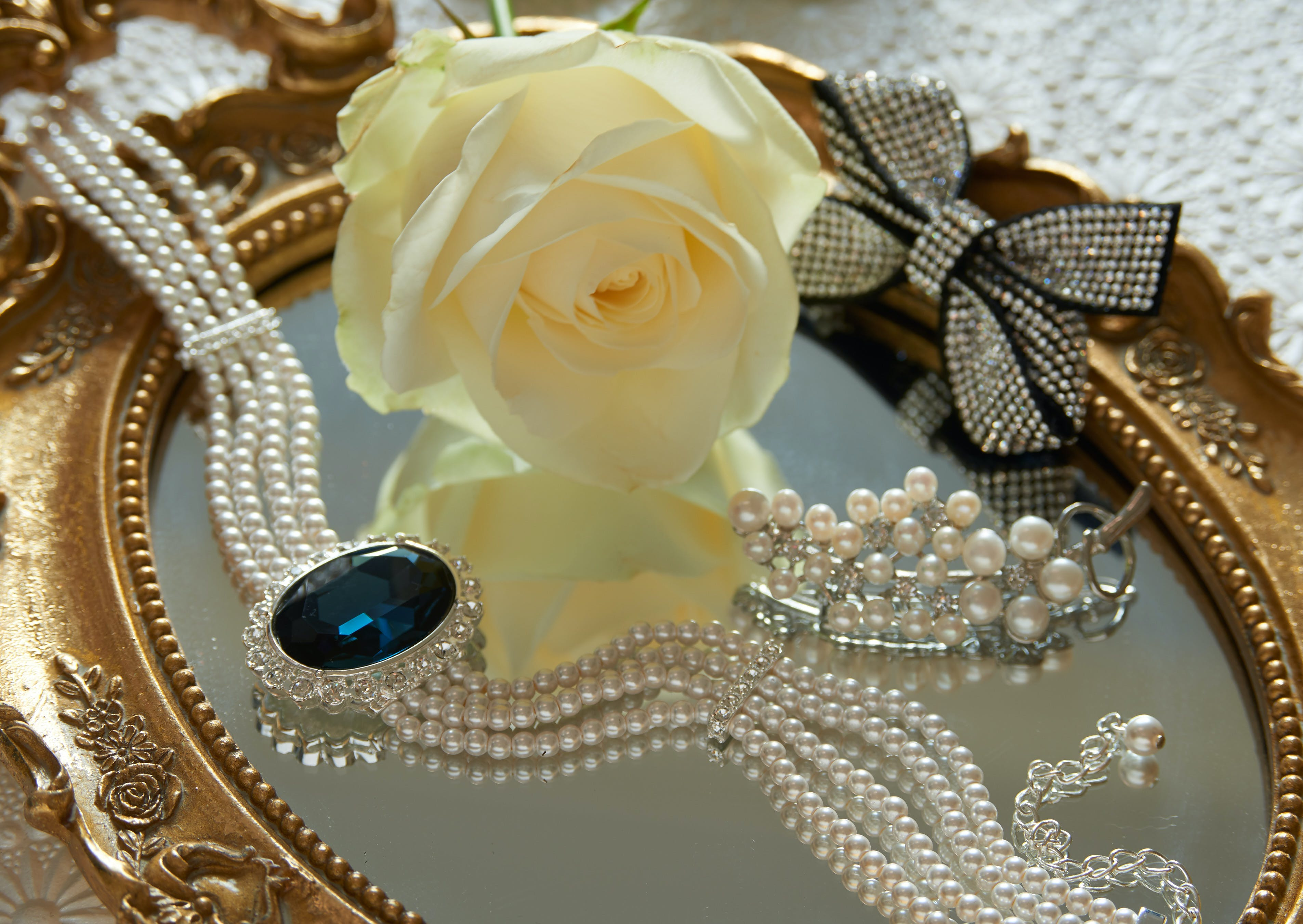 Lifestyle setting, gifts for her.  Faux sapphire choker, Diamante floral spray brooch and sterling silver brooch with diamante accents in classic bow shape.