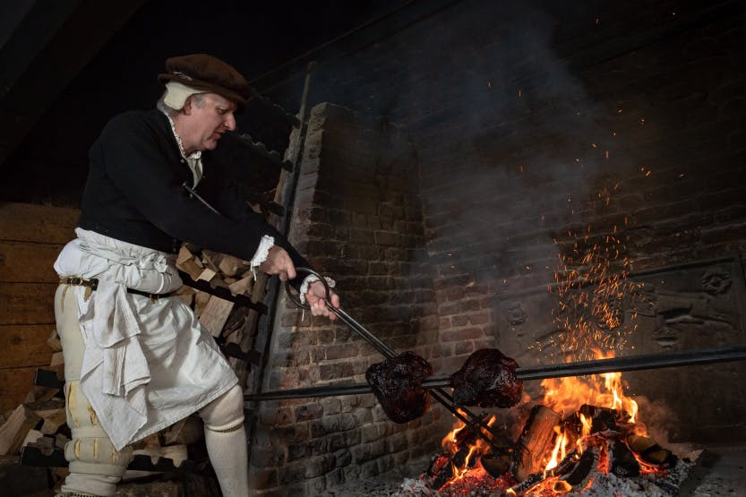 Cook at Hampton Court Palace roasting meat in the kitchens