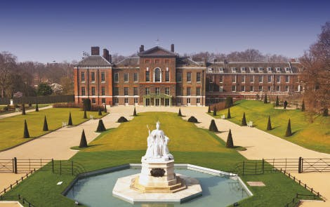 East front of Kensington Palace with a blue sky and gardens in the foreground