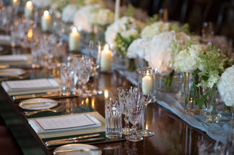 A close-up of the State Dining Room table dressed elegantly with a central runner, flowers, crystal glassware and silver cutlery.