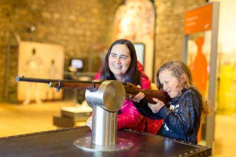 A woman and child interact with an armoury exhibit in Armoury in Action within the White Tower of the Tower of London