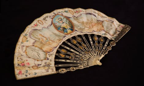 An English paper fan, photographed on a black background. The fan is decorated with landscapes, a shepherd and shepherdess and grisaille medallions of putti.  The fan has sticks of ivory arranged in pairs: one pair carved, pierced and gilded, one pair composed of three medallions. The medallions incorporate motifs of birds, putti, urns and portraits.