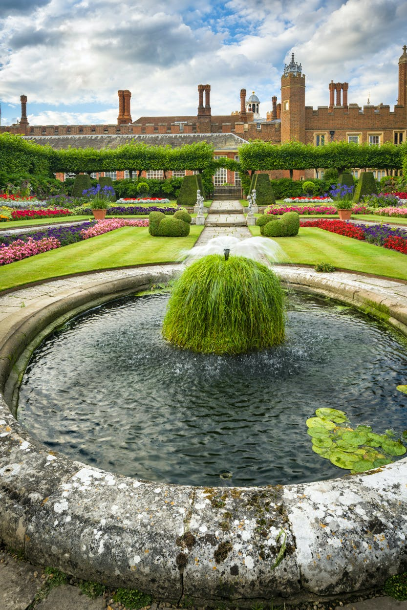 Portrait image of The Pond Gardens at Hampton Court Palace with fountain in the foreground and palace in the background