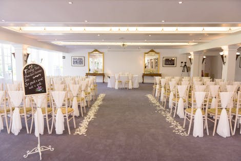 White chairs laid out for a civil ceremony in a bright white events space with grey carpet