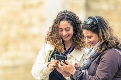 The Tower of London, looking north-west. Showing two female visitors using the digital audio guide tour devices.