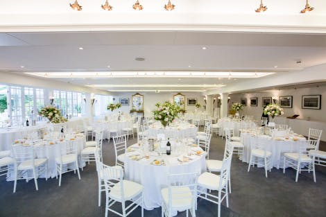 Tables arranged for a wedding breakfast in a bright white event space, decorated with white tablecloths and floral displays