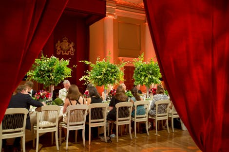 Dinner guests eat in the Banqueting Hall under a red canopy