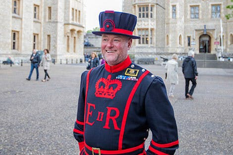 Yeoman Warder J Woodcock is shown in his full uniform with the Royal Fusilier's Museum and Waterloo Block in the distance