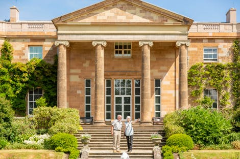 A couple on the South Terrace enjoying views of the gardens at Hillsborough Castle. The South Façade of the castle is clearly visible in the background. The water fountain of the jubilee Parterre rises-up in the foreground. A blue sky hangs above.
