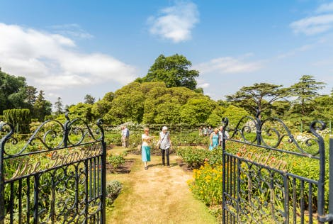A group of visitor enjoy a wander around the Granville Garden in the grounds of Hillsborough Castle on a warm Summers Day. The open iron gates of the garden are visible in the foregrouns and a blue clouded sky above is in start contract to the bright green of Europe's largest rhododendron, also visible behind the garden.