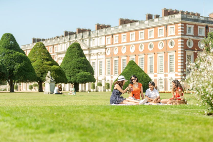 A family of two women, a boy and a girl relax in the Great Fountain Garden at Hampton Court Palace with a picnic. The baroque East Front can be seen in the background