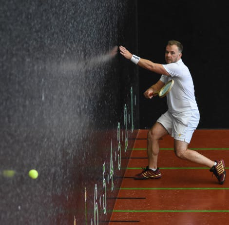 A real tennis player strikes a tennis ball across the court during a match