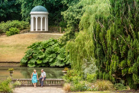 A middle-aged couple sit on balustrade in front of the pond in front of Lady Alice's Temple. The white, columned temple sits elevated above the pond which is surrounded by mature plans.