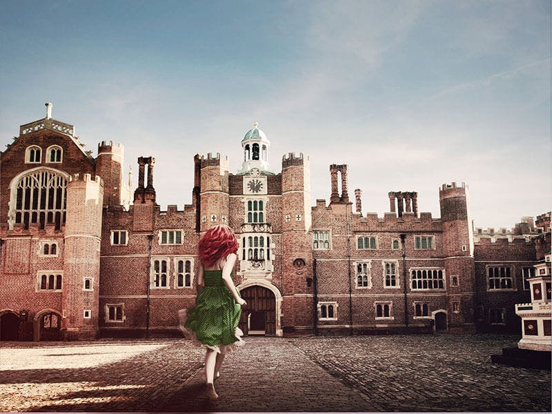 A woman with red hair runs through Base Court showing the Tudor apartments at Hampton Court Palace