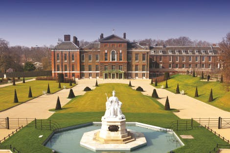 The east front of Kensington Palace and gardens with the statue of Queen Victoria in the foreground, under a blue sky.