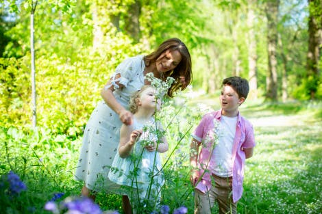 A woman and her two children enjoy the gardens of Hillsborough Castle and Gardens on a bright sunny day