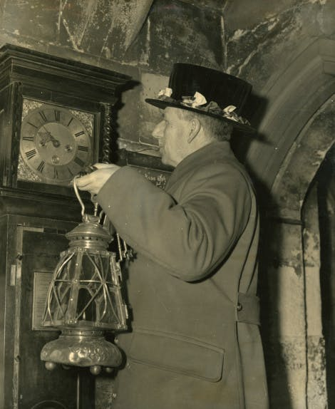 The Ceremony of the Keys. Chief Yeoman Warder, A H Cook, lantern and keys in hand, checks the time in preparation for the start of the ceremony