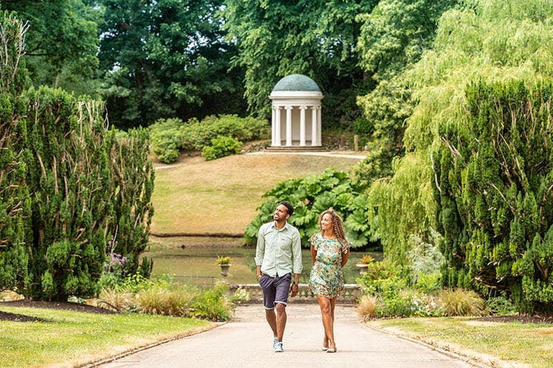 Young male and female couple stroll up a tree-lined path from a historic temple building in the background. A lake and lush green trees line the background of the image.
