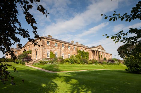 An exterior photo of the South facade of Hillsborough Castle on a sunny September day. Framed by greenery.