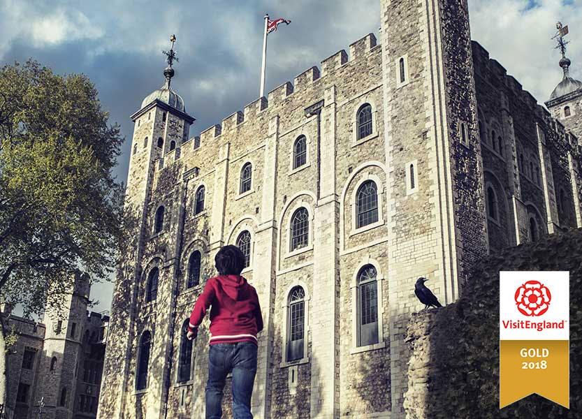 Boy runs towards the White Tower at the Tower of London under a gloomy sky. The Visit England Gold sits in the bottom-right hand corner of the image.