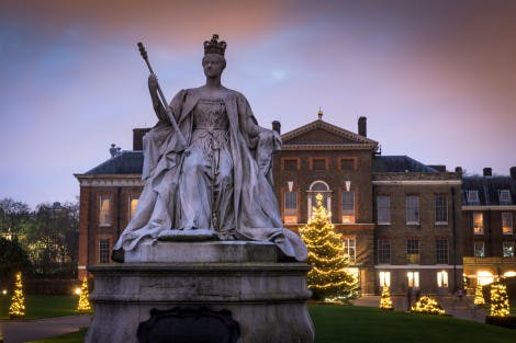 A view of Kensington Palace at twilight with Christmas trees and lights on the front of the palace