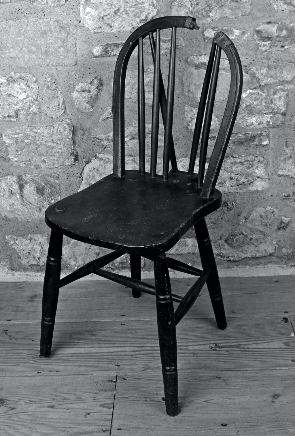 Black and white photograph of a windsor chair with bow rail originally supported by 6 spindles with 2 set at a slight angle to brace behind. Slightly shaped upper surface to seat. Legs tapered at either end with turned plain moulding above and below the mid section. Re-inforced by 2 side stretchers, a back and middle stretcher.  Two of the spindles forming the back have been shot away and part of the back rail.